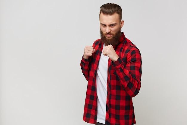 Jovem bonito barbudo com uma pose raivosa, agressiva e ameaçadora, pronto para a luta, mostrando os punhos furiosamente e beligerantemente.