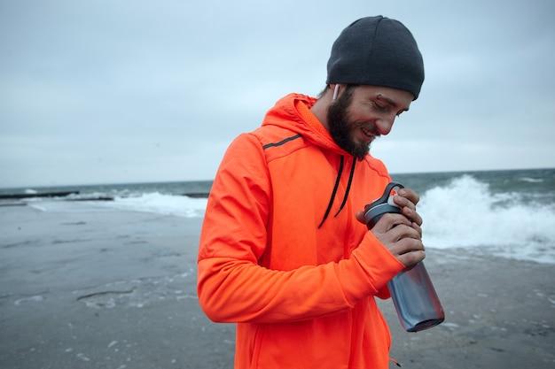 Jovem bonito barbudo de cabelos escuros entra para o esporte todas as manhãs, indo à beira-mar com uma garrafa de fitness nas mãos levantadas e sorrindo positivamente. esporte e conceito de estilo de vida saudável