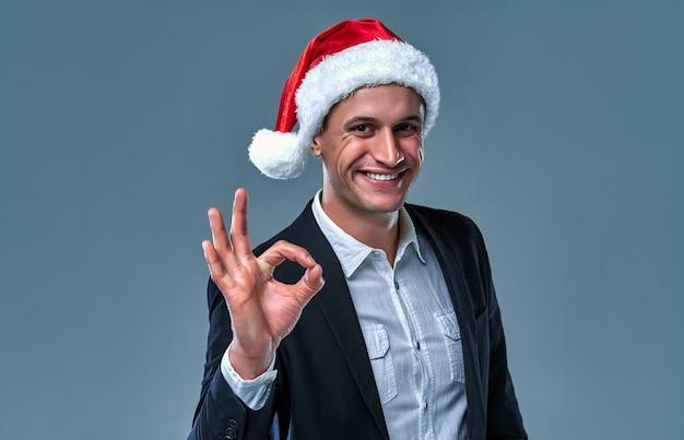 Jovem bonito barbudo em suíte com chapéu vermelho de natal, diga ok em fundo cinza. feliz natal e feliz ano novo nos negócios