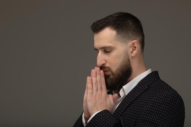 Jovem bonito barbudo homem contra uma parede cinza, segurando as mãos em rezar perto da boca, sente-se confiante.