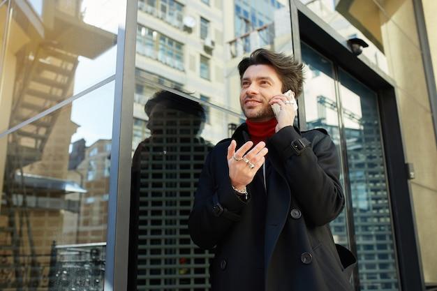 Jovem bonito barbudo homem moreno com roupas elegantes, mantendo o celular na mão levantada enquanto tem uma conversa agradável, isolado sobre o fundo da cidade