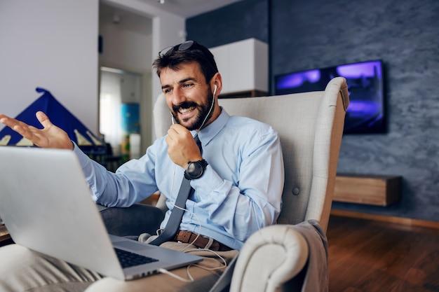 Jovem bonito barbudo pai vestido elegante sentado na cadeira em casa e usando o laptop para chamada em conferência.