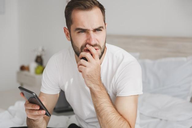 Jovem bonito barbudo sentado na cama com lençol branco e cobertor no quarto em casa