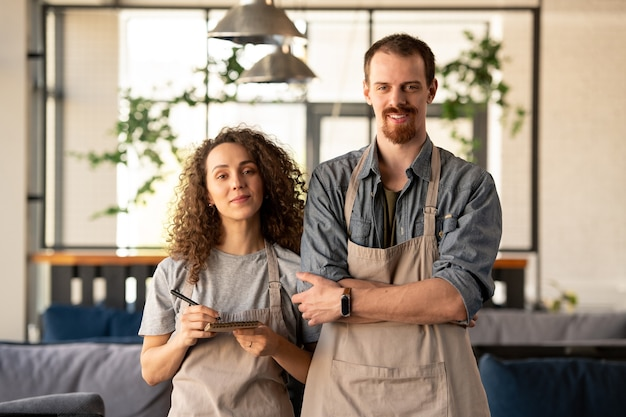Jovem bonito barbudo sorridente com camisa jeans digitando em um laptop moderno enquanto trabalhava em um café
