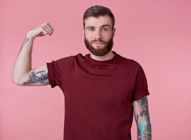 Jovem bonito barbudo vermelho com uma camiseta em branco, de pé sobre um fundo rosa, parece legal, se diverte e demonstra poder, olha para a câmera e sorri