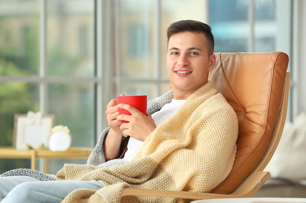 Jovem bonito bebendo chá em casa