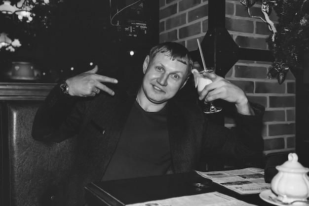 Jovem bonito bebendo coquetel no bar noturno na mesa, olhando para a câmera e sorrindo. conceito de estilo de vida de cidade noturna de vida noturna. copie o espaço
