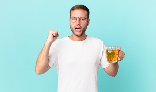 Jovem bonito bebendo meio litro de cerveja