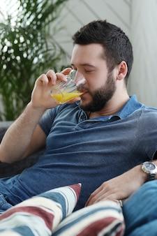 Jovem bonito bebendo suco de laranja em casa