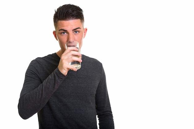 Jovem bonito bebendo um copo d'água