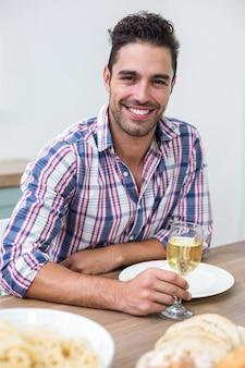 Jovem bonito bebendo vinho na mesa
