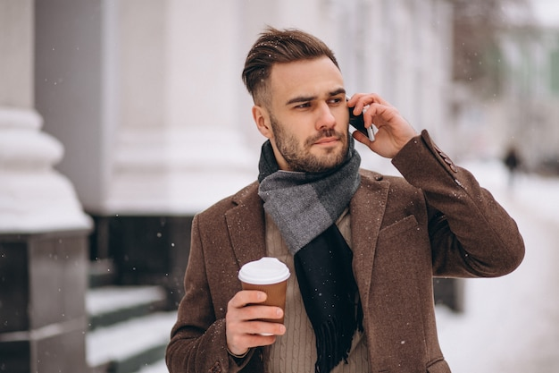 Jovem bonito beber café e falando no telefone