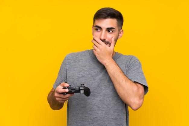 Jovem bonito, brincando com um controlador de videogame, pensando em uma idéia