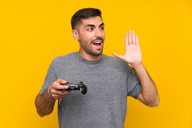 Jovem bonito brincando com um controlador de videogame sobre parede amarela isolada gritando
