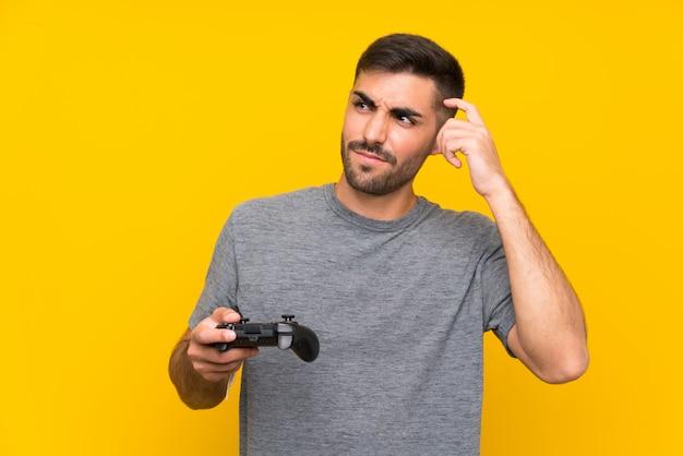 Jovem bonito brincando com um controlador de videogame sobre parede amarela isolada, tendo dúvidas e com a expressão do rosto confuso
