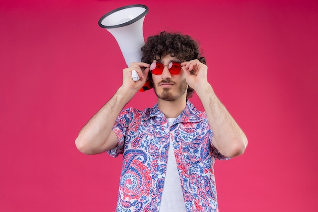 Jovem bonito cacheado confiante usando óculos escuros, colocando as mãos neles e segurando o alto-falante no espaço rosa isolado com espaço de cópia