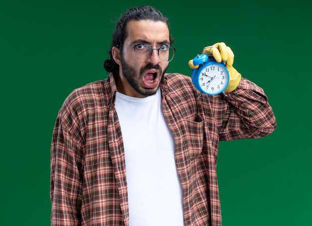 Jovem, bonito, cara de limpeza assustado, vestindo camiseta e luvas, segurando um despertador isolado na parede verde