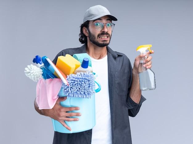 Jovem, bonito, cara de limpeza preocupado, vestindo camiseta e boné, segurando um balde de ferramentas de limpeza com um frasco de spray isolado na parede branca