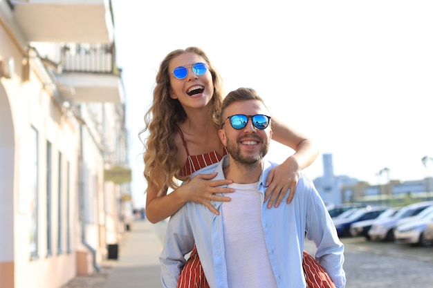Jovem bonito carregando uma mulher atraente nos ombros enquanto passam algum tempo juntos ao ar livre.