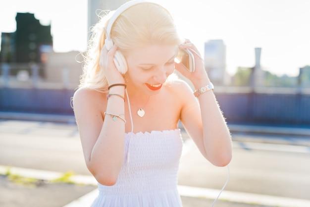 Jovem bonito caucasiano longo loiro cabelo liso mulher dançando nas ruas da cidade