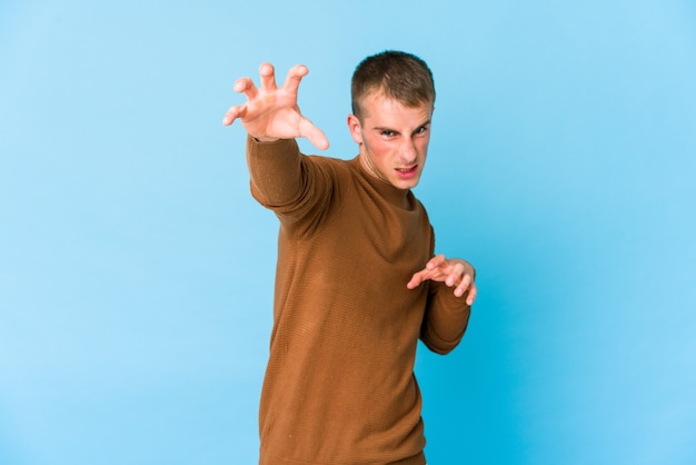 Jovem bonito caucasiano mostrando garras imitando um gato, gesto agressivo.