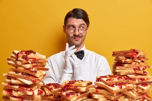 Jovem bonito cercado por sanduíches de gelatina de manteiga de amendoim