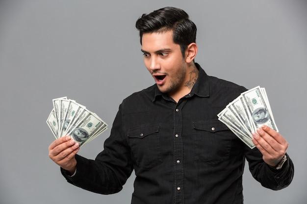 Jovem bonito chocado segurando o dinheiro.