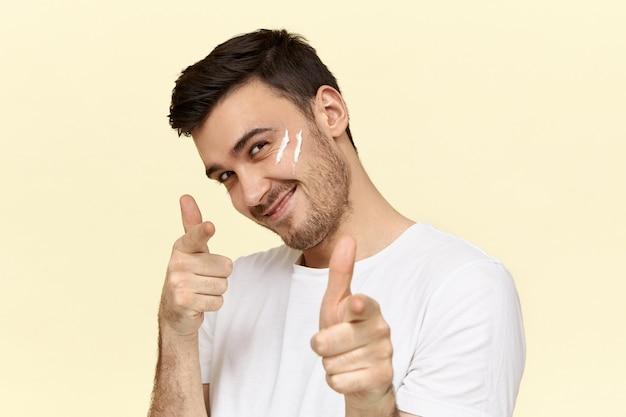 Jovem bonito com a barba por fazer em uma camiseta branca sorrindo e apontando o dedo indicador para a frente