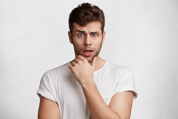Jovem bonito com a barba por fazer parece perplexo, mantém a mão no queixo, insatisfeito