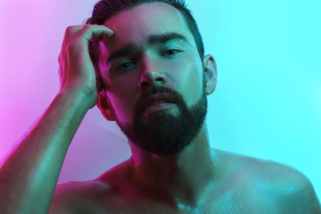 Jovem bonito com a pele molhada em luz neon