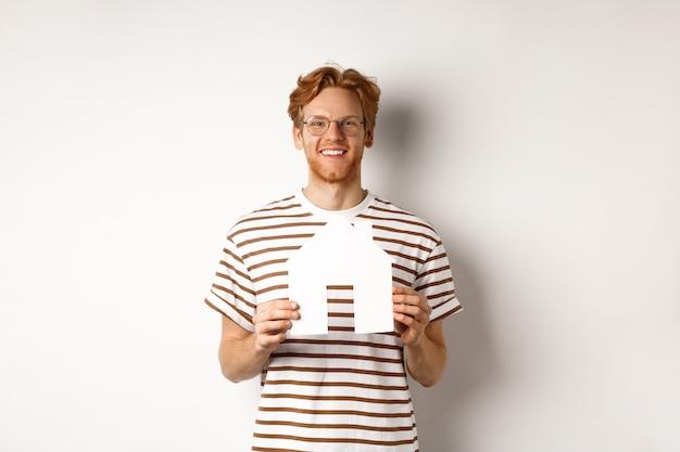 Jovem bonito com barba e cabelo ruivo, usando óculos e camiseta listrada, mostrando o recorte da casa de papel e sorrindo, conceito de imóveis e compra de imóveis.