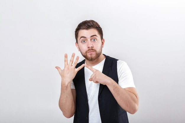 Jovem bonito com barba em uma camisa branca e um colete preto mostrando o gesto de número cinco