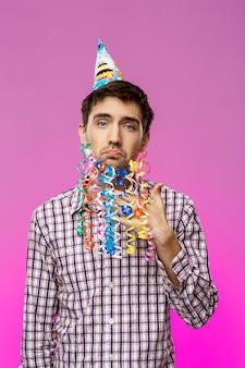 Jovem bonito com barba falsa posando na festa de aniversário.