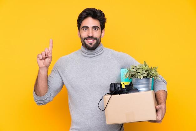 Jovem bonito com barba, fazendo um movimento ao pegar uma caixa cheia de coisas ao longo da parede isolada, apontando uma ótima idéia