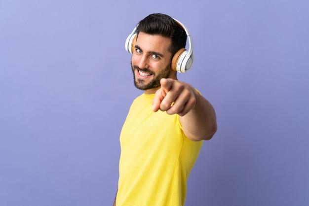 Jovem bonito com barba isolada na parede roxa, ouvindo música e apontando para a frente