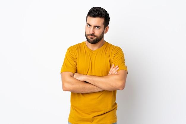 Jovem bonito com barba isolada no fundo branco com expressão infeliz