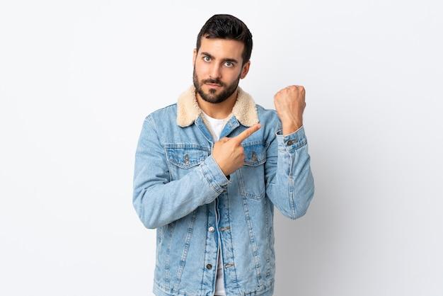Jovem bonito com barba isolada no fundo branco fazendo o gesto de estar atrasado