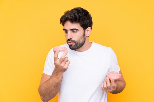 Jovem bonito com barba isolado parede amarela segurando um donut
