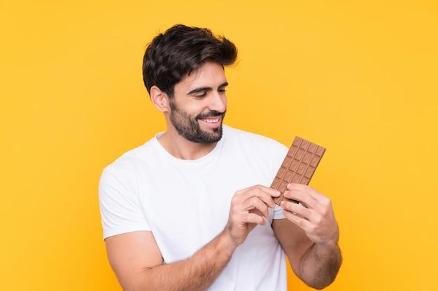 Jovem bonito com barba isolado parede amarela tomando uma tablete de chocolate e feliz