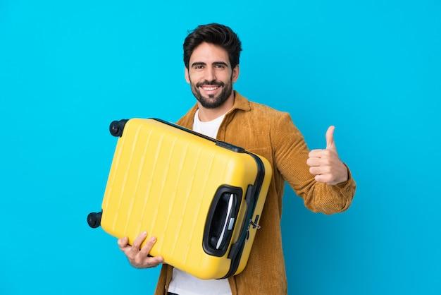 Jovem bonito com barba isolado parede azul em férias com mala de viagem e com o polegar para cima