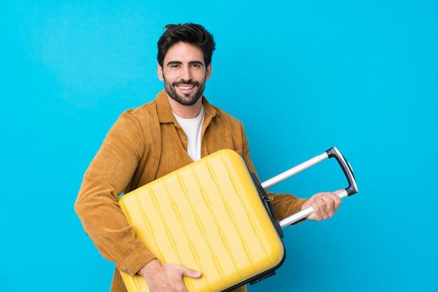 Jovem bonito com barba isolado parede azul em férias com mala de viagem