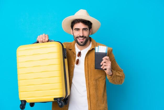 Jovem bonito com barba isolado parede azul em férias com mala e passaporte