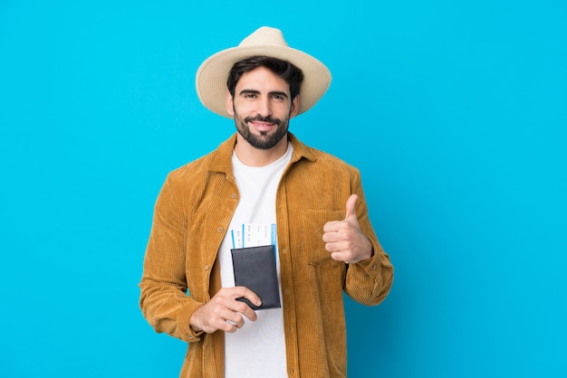 Jovem bonito com barba isolado parede azul em férias segurando um passaporte e avião com o polegar