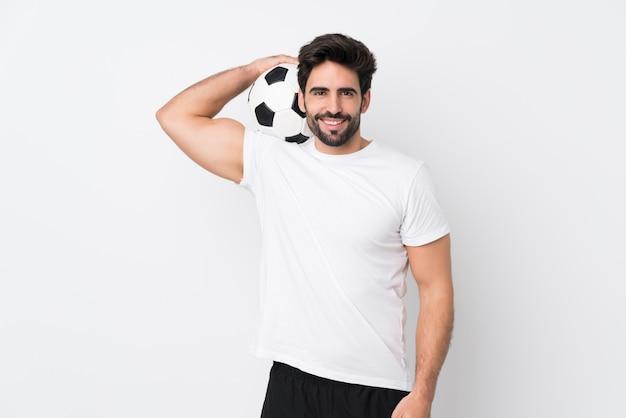 Jovem bonito com barba isolado parede branca com bola de futebol