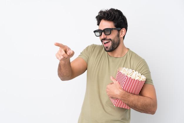 Jovem bonito com barba isolado parede branca com óculos 3d e segurando um grande balde de pipocas enquanto apontando a frente