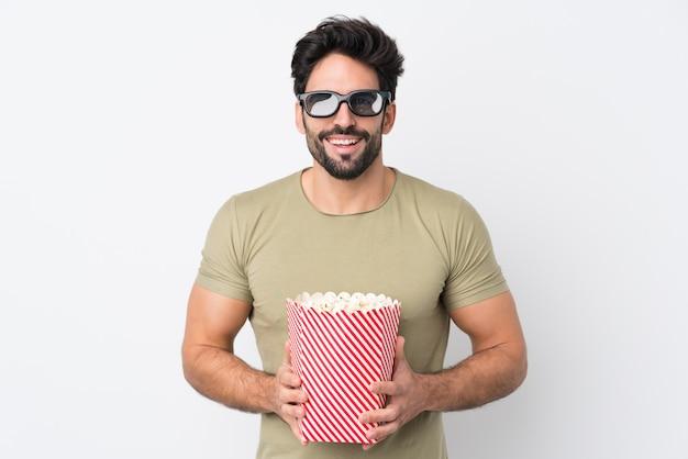Jovem bonito com barba isolado parede branca com óculos 3d e segurando um grande balde de pipocas