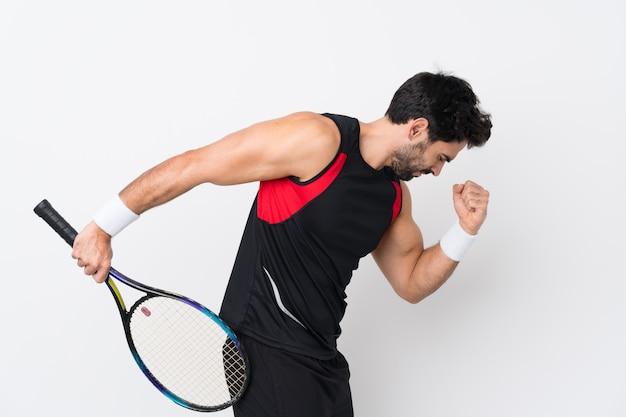 Jovem bonito com barba isolado parede branca jogando tênis e comemorando uma vitória