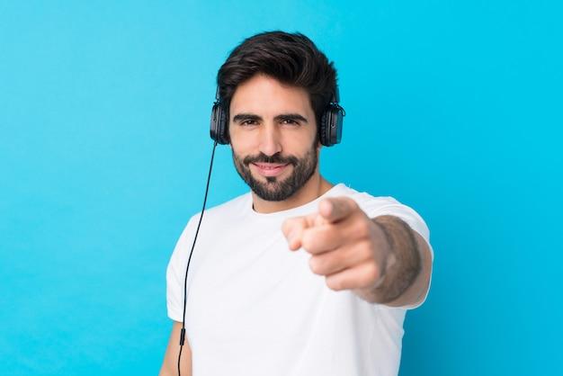 Jovem bonito com barba, ouvindo música de parede azul isolado e apontando para a frente
