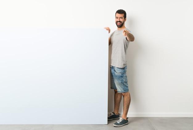 Jovem bonito com barba, segurando um cartaz grande azul vazio aponta o dedo para você com uma expressão confiante