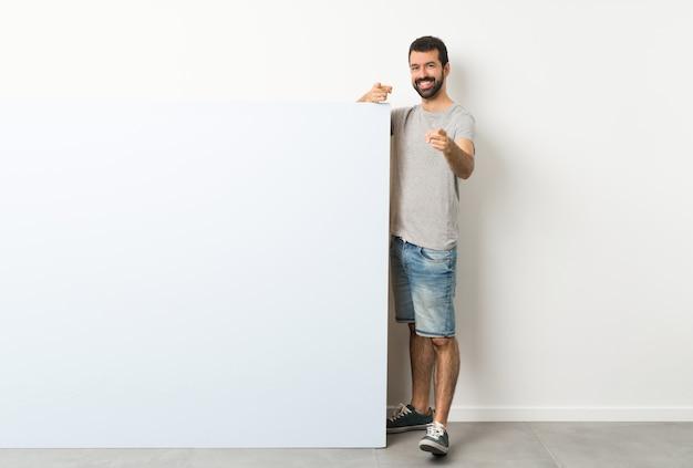 Jovem bonito com barba segurando um cartaz grande azul vazio aponta o dedo para você enquanto sorrindo